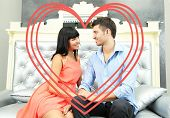 Beautiful young romantic couple and heart-shaped frame sitting on sofa