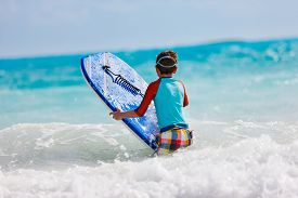 pic of boogie board  - Little boy on vacation having fun surfing on boogie board - JPG