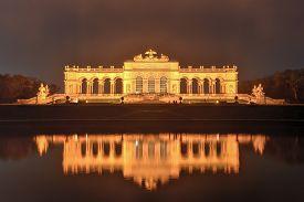 stock photo of schoenbrunn  - Gloriette in Schoenbrunn Palace Gardens Vienna Austria at night as it reflects in the water - JPG