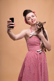 pic of pale skin  - Portrait of pretty brunette  girl in rose dress and red headband in retro style  with Chihuahua doing selfie smiling looking at phone  waist up - JPG