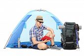 foto of camper  - Young male camper reading a book seated on the ground with a blue tent behind him and a large backpack beside him isolated on white background - JPG