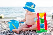 stock photo of pretty-boy  - cute toddler boy playing on the beach in summer - JPG
