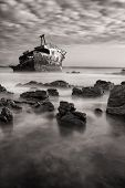 stock photo of shipwreck  - Old shipwreck long exposure on the rocks at sunset artistic conversion