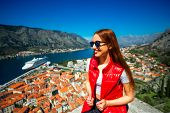 stock photo of vest  - Young woman traveler in red vest with backpack on the Lovcen mountain near the old city Kotor - JPG