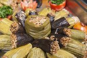 stock photo of buffet  - Closeup detail of dolma stuffed vegetables on display at an oriental restaurant buffet - JPG