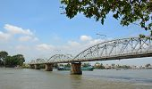 stock photo of old bridge  - Bien Hoa Vietnam - Apr 5 2015. Old railway bridge and cargo boat on Dong Nai river Bien Hoa southern Vietnam.