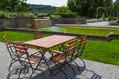 picture of lawn chair  - wooden table and chairs in a beautiful park with ornamental pool - JPG