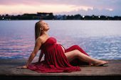 picture of bump  - A seated profile portrait of beautiful pregnant woman wearing a red maternity gown that slightly exposes her baby bump - JPG