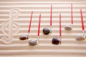stock photo of g clef  - Festive music at the beach background concept with notes of waterworn pebbles and red paintbrushes overlying a score of alternating rows of colored sand with a hand drawn G clef in an artistic design - JPG