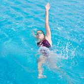 pic of crawling  - Young girl in goggles and cap swimming back crawl stroke style in the blue water pool - JPG