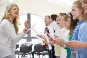 stock photo of 11 year old  - Children In Singing Group Being Encouraged By Teacher - JPG