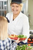 stock photo of pupils  - Pupil In School Cafeteria Being Served Lunch By Dinner Lady - JPG