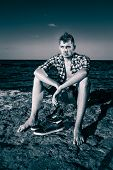 stock photo of nearly nude  - Attractive young fashion sexy man sitting on a rock near the sea water with shoes beside him in black and white - JPG