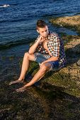 foto of nearly nude  - Attractive young fashion sexy man sitting on a rock near the sea water - JPG