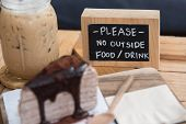 picture of serving tray  - fresh iced coffee and delicious chocolate crape cake serve on wooden tray in coffee shop - JPG