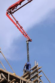 pic of boom-truck  - Builder worker with tube from truck mounted concrete pump pouring cement into formwork reinforcement - JPG