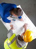 Two Builders Discuss Construction Blueprints