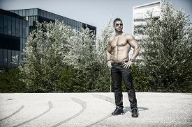 stock photo of hunk  - Handsome Muscular Shirtless Hunk Man Outdoor in City Setting. Showing Healthy Body While Looking At Camera