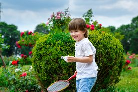stock photo of shuttlecock  - Play badminton. Portrait of happy little boy holding badminton racket and shuttlecock while standing on green grass.
