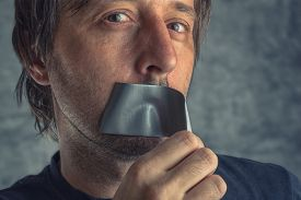 foto of freedom speech  - Fighting censorship adult caucasian man removing duct tape from mouth that prevented him from speaking freedom of speech and expression concept - JPG