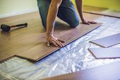 Man Installing New Wooden Laminate Flooring. Infrared Floor Heating System Under Laminate Floor poster