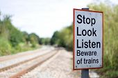 Warning sign next to a high speed railway line advising pedestrians to Stop, Look and Listen before