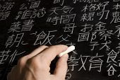 Close up of male hand writing Chinese and Japanese characters on blackboard. The words in Japanese have random meanings.