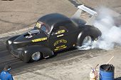 CHANDLER, AZ - OCTOBER 2: A hot rod car burns out before the start of the race in the NHRA Pacific D