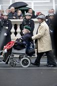 WHITEHALL, LONDON - NOV 8:A man pushes a veteran in his wheelchair  during the Royal British Legion
