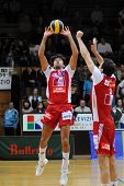 KAPOSVAR, HUNGARY - DECEMBER 8: Guilherme (with the ball) posts the ball at a CEV Cup volleyball gam