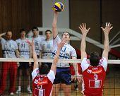 KAPOSVAR, HUNGARY - JANUARY 22: Istvan Schulcz (C) strikes the ball at a Middle European League volleyball game Kaposvar (HUN) vs. HotVolleys Wien (AUT), January 22, 2010 in Kaposvar, Hungary.