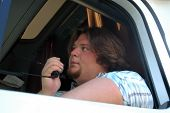 stock photo of 18 wheeler  - Truck driver sitting in truck holding microphone talking on C - JPG