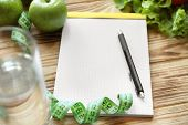 Blank notebook, pen, measuring tape and healthy products on wooden table. Weight loss concept poster