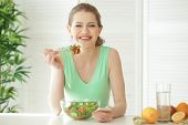 Young woman using mobile phone for counting calories while eating salad. Weight loss concept poster