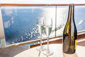 Champagne bottle and flutes glasses on luxury cruise travel for honeymoon holidays. Boat at sea on v poster