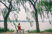 Nature lake woman sitting on park bench relaxing at view of Summer Palace in Beijing, China. Asia tr poster