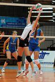 KAPOSVAR, HUNGARY - OCTOBER 10: Rita Bodnar (C) posts the ball at the Hungarian NB I. League woman volleyball game Kaposvar vs Veszprem, October 10, 2010 in Kaposvar, Hungary.