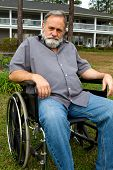 image of crippled  - Disabled crippled man sits in his wheelchair in front of his home in the grass - JPG