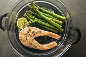 Steamed Salmon With Fresh Herbs. Fresh Meal With Salmon File With Asparagus On Steam. Steam Salmon S poster