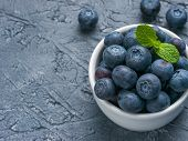 Freshly Picked Blueberries Closeup. Ripe And Juicy Fresh Blueberry With Green Mint Leaves On Texture poster