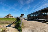 Bus On Road To Famous Mont Saint Michel Abbey. It Is One Of The Most Famous Tourist Attractions In F poster