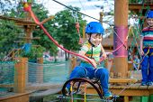 Little Cute Boy Enjoying Activity In A Climbing Adventure Park On A Summer Sunny Day. Toddler Climbi poster