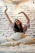 Young Happy Woman Stretching In Bed After Wake Up In Her Modern Apartment. Good Morning, Carefree Co poster