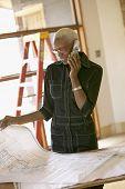 Young businesswoman examining blueprints