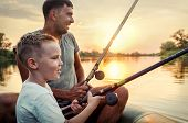 Happy Father and Son together fishing from a boat at sunset time in summer day under beautiful sky o poster