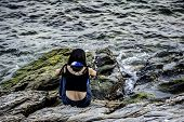 Girl Sit On Large Rock On Coast Of Sea, Alone Concept Of One Girl Sit Beside Sea, Transquil Sea With poster