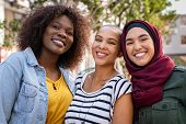 Group of three happy multiethnic friends looking at camera. Portrait of young women of different cul poster