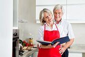 Happy senior Couple in Kitching Rezepte in einem Kochbuch gesucht
