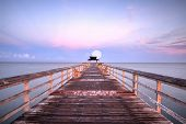 Moonset At Early Sunrise Over The Naples Pier On The Gulf Coast Of Naples, Florida In Summer. poster