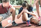 Female Athlete Getting Injured During Athletic Run Training - Male Coach Taking Care On Sport Pupil  poster